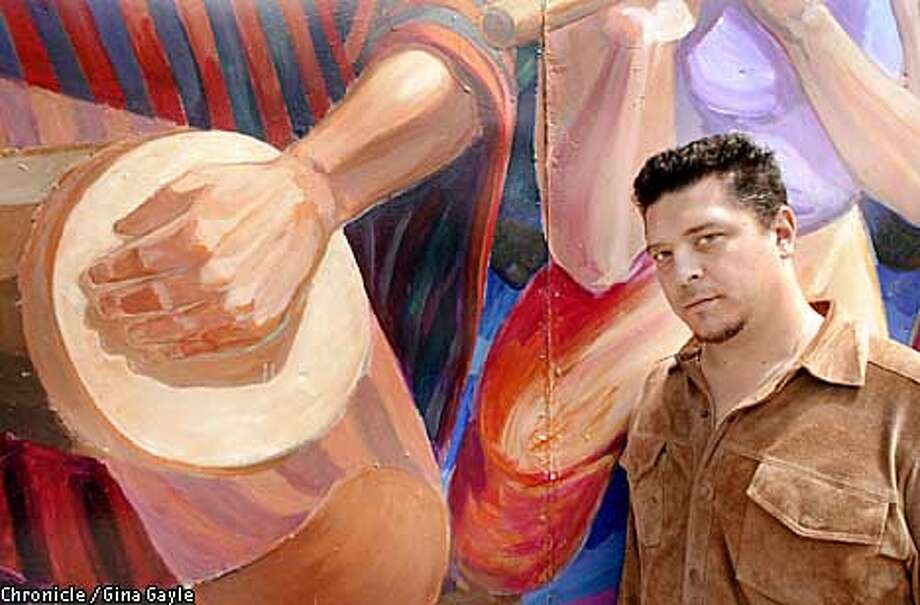 Actor paul Flores of the Los Delicados spoken word group stand outside the mural at La Pena Cultural Center in Berkeley. Photo by Gina Gayle/The SF Chronicle. Photo: GINA GAYLE