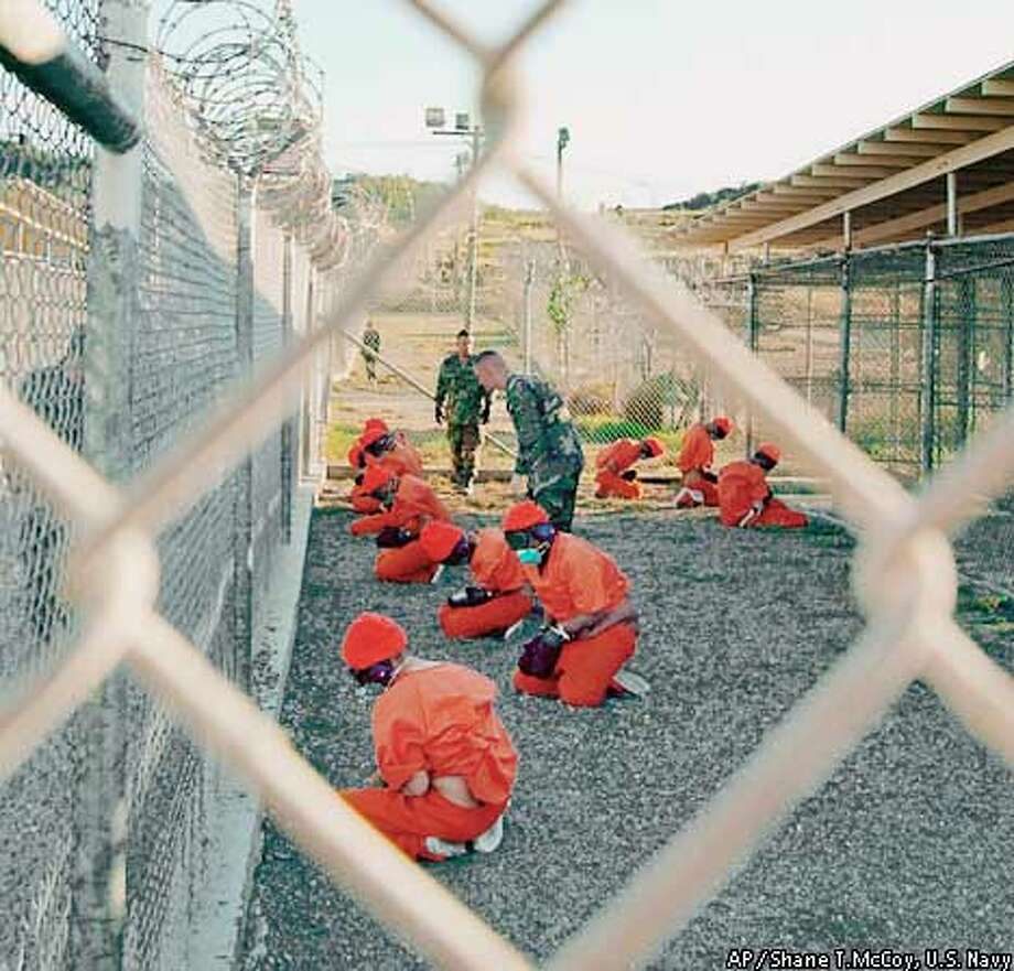 RETRANSMISSION FOR ALTERNATE CROP--In this handout photo from the Department of Defense made available Friday Jan. 18, 2002, Taliban and al-Qaida detainees in orange jumpsuits sit in a holding area under the watchful eyes of military police at Camp X-Ray at Naval Base Guantanamo Bay, Cuba, during in-processing to the temporary detention facility on Jan. 11, 2002. The detainees will be given a basic physical exam by a doctor, to include a chest x-ray and blood samples drawn to assess their health, the military said. (APPhoto/Shane T.McCoy, U.S. Navy) Photo: SHANE T. MCCOY