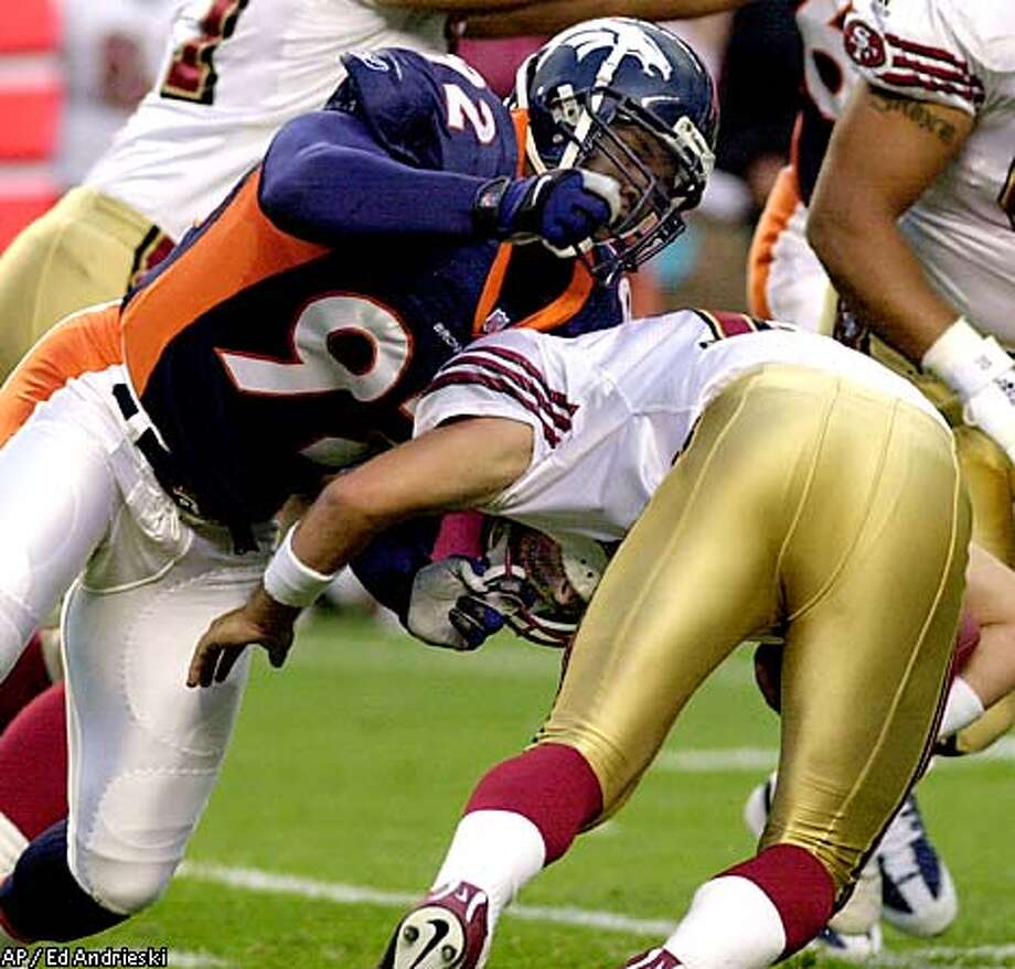 Denver Broncos defensive end Berry Bertrand, left, sacks San Francisco 49ers quarterback Tim Rattay during the first quarter of an NFL exhibition game in Denver on Friday night, Aug. 31, 2001. Bertrand was penalized 15 yards for grabbing Rattay's face mask on the play. (AP Photo/Ed Andrieski) Photo: ED ANDRIESKI