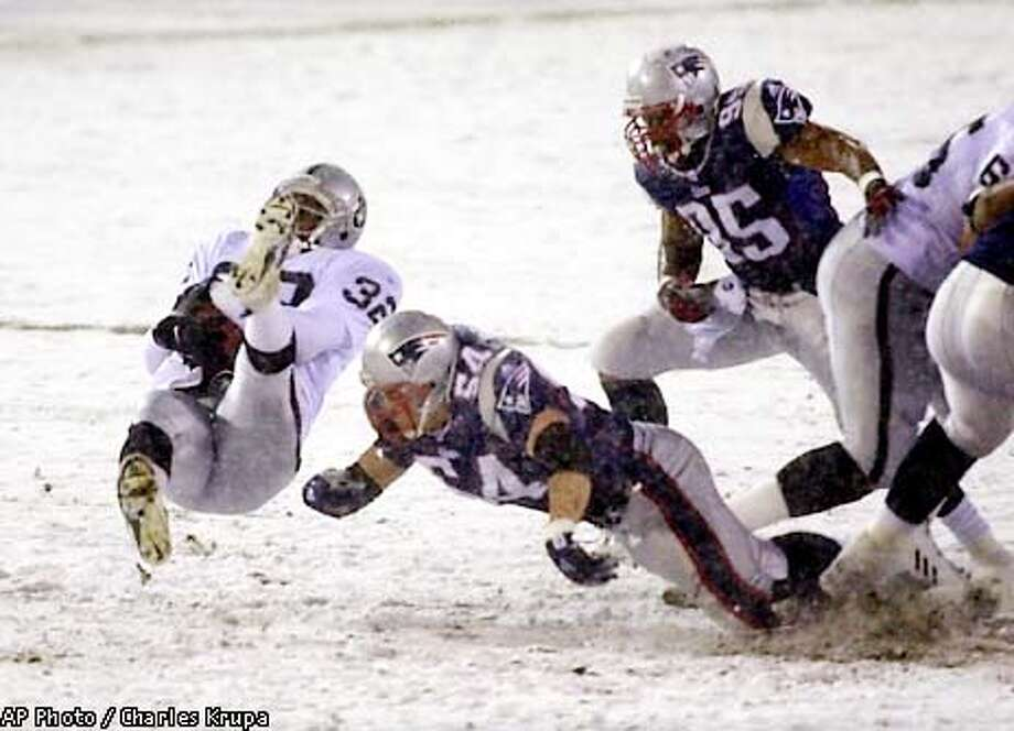 New England Patriots linebacker Tedy Bruschi (54) cuts out the legs of Oakland Raiders running back Zack Crockett, left, as Patriots linebacker Roman Phifer (95) looks on during the first quarter of the AFC Divisional Playoff game at snowy Foxboro Stadium, in Foxboro, Mass., Saturday, Jan. 19, 2002. (AP Photo/Charles Krupa) Photo: CHARLES KRUPA