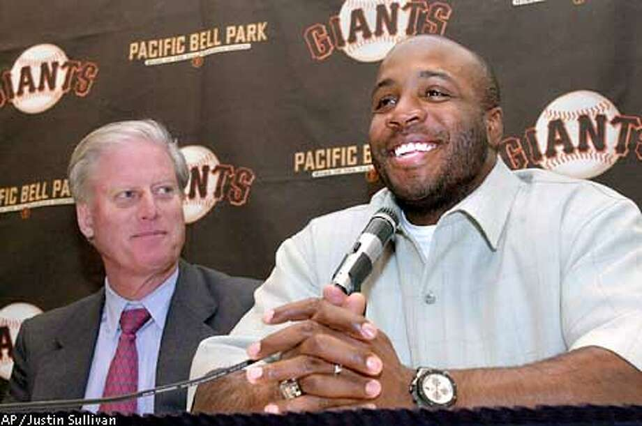 San Francisco Giants' Barry Bonds laughs during a news conference to announce his re-signing with the Giants in San Francisco on Monday Jan. 14, 2002. Bonds' five-year contract is worth $90 million. Giants owner Peter MacGowan looks on at left. (AP Photo/Justin Sullivan) Photo: JUSTIN SULLIVAN
