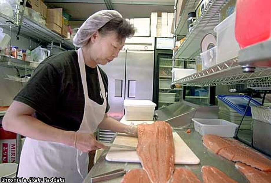 Photo by Katy Raddatz--The Chronicle  Kitaro Sushi, 5723 Geary in SF. Nancy Yim prepares fresh salmon. Photo: KATY RADDATZ