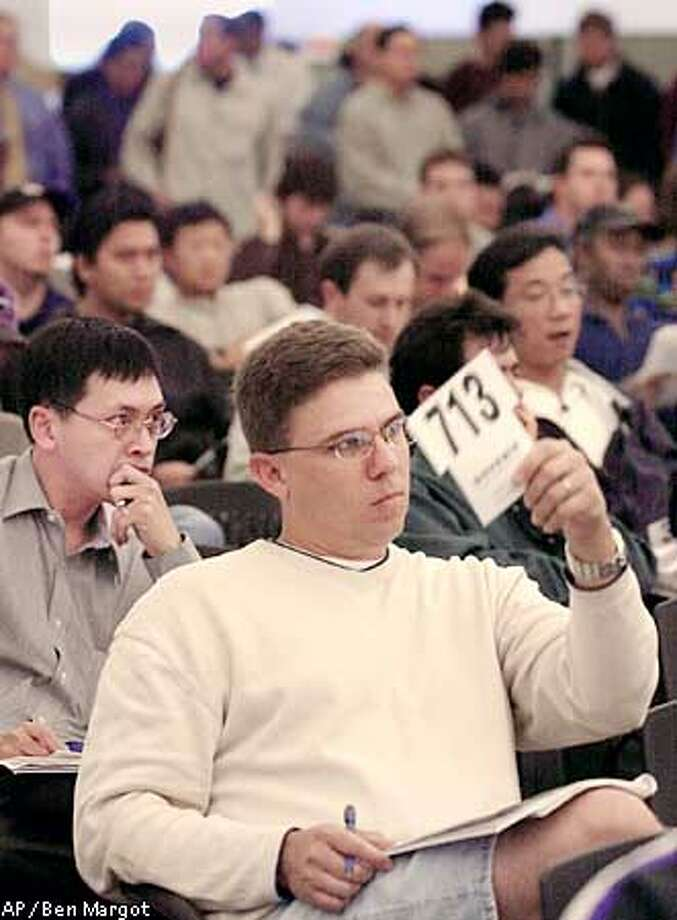 FILE--Steve Spagnola, of San Jose, Calif., bids during the bankrupt online grocer Webvan Group Inc., auction Oct. 30, 2001, at Webvan corporate headquarters in Foster City, Calif. The economy in the western United States is 1.5 times more dependent on the technology industry than the rest of the country, according to a new analysis by the Federal Reserve Bank, shedding some light on why the San Francisco Bay area and Washington state have been so hard hit by this year's high-tech slump. (AP Photo/Ben Margot, File) Photo: BEN MARGOT