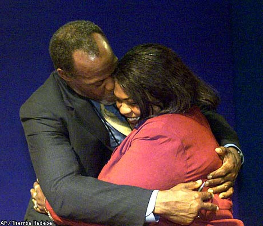 """Actor and United Nations Goodwill Ambassador Danny Glover, left, embraces Sarah White, right, of the U.S., after she told of her experiences of exploitation by employers in catfish plants throughout the Mississippi Delta, during special forum called the """"voices"""", on the fifth-day of the World Conference Against Racism in Durban, South Africa, Tuesday Sept. 4, 2001. (AP Photo/Themba Hadebe) Photo: THEMBA HADEBE"""