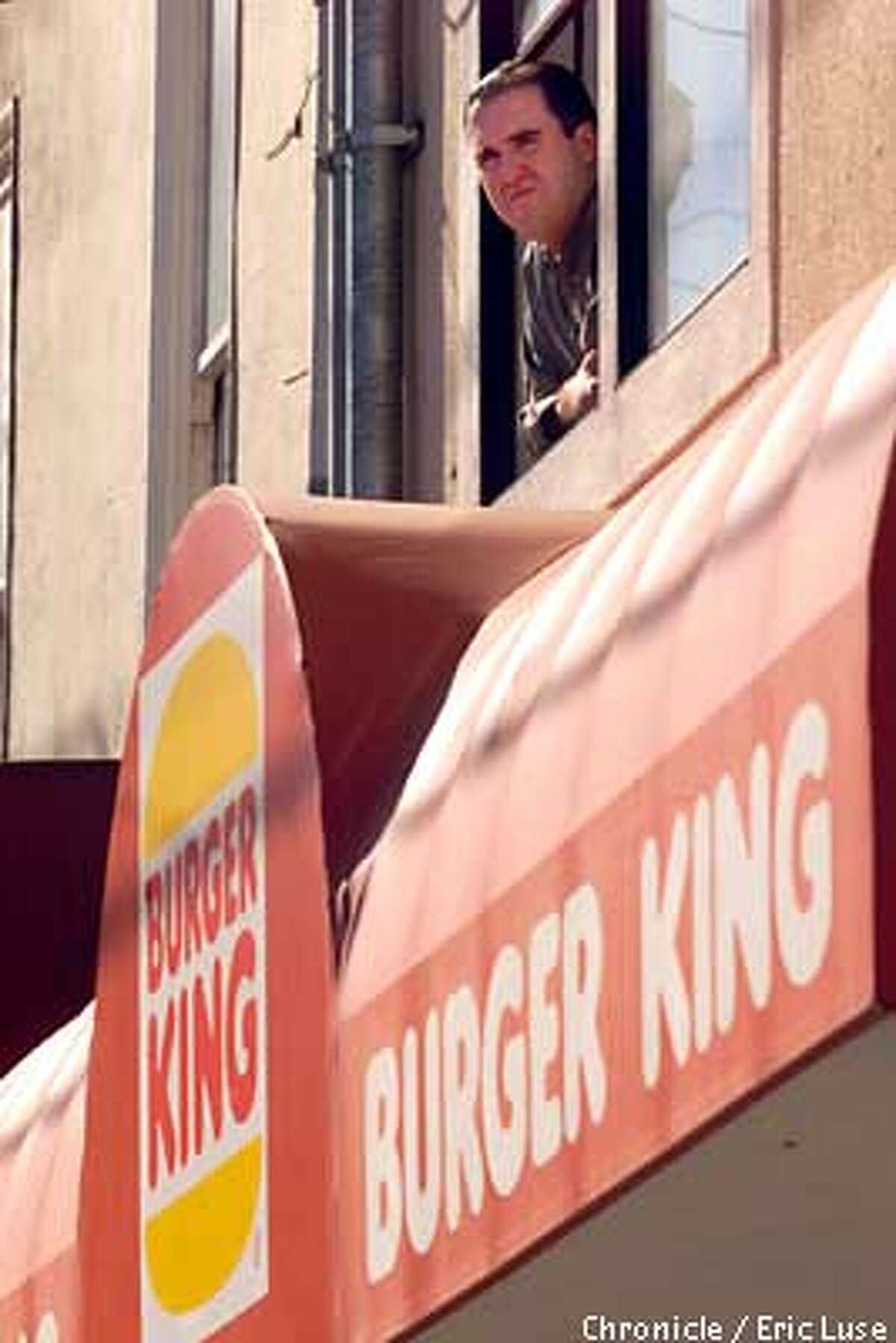 Owne Travers looking out his apartment window on 9th Avenue near Irving where he is directly above Burger King. BY ERIC LUSE/THE CHRONICLE