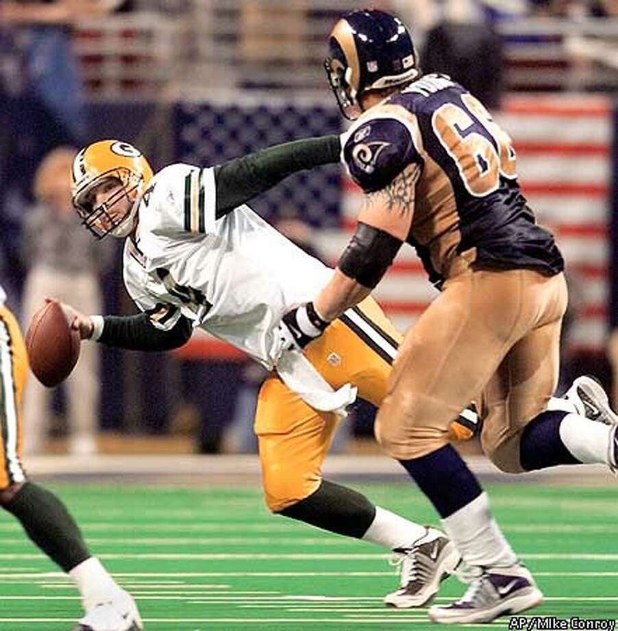Green Bay Packers' quarterback Brett Favre (4) attempts to avoid St. Louis Rams' defensive end Brian Young (66) while trying to pass during the second quarter of their NFC divisional playoff game in St. Louis, Sunday, Jan. 20, 2002. (AP Photo/MIke Conroy) Photo: MIKE CONROY