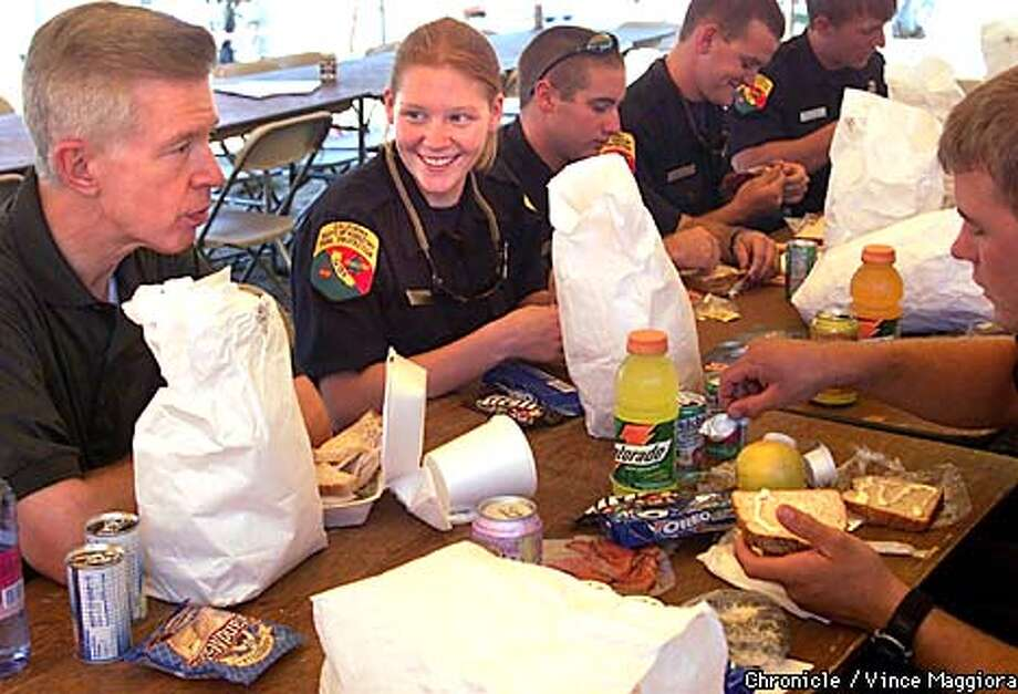 cdf firefighter Anna Stewart talkinf and eating lunch with Gov Gray Davis at the CDF base camp. .Oregon fire in Weaverville, Trinity County destroyed homes and mass evacuations .  by Vince Maggiora Photo: VINCENT MAGGIORA