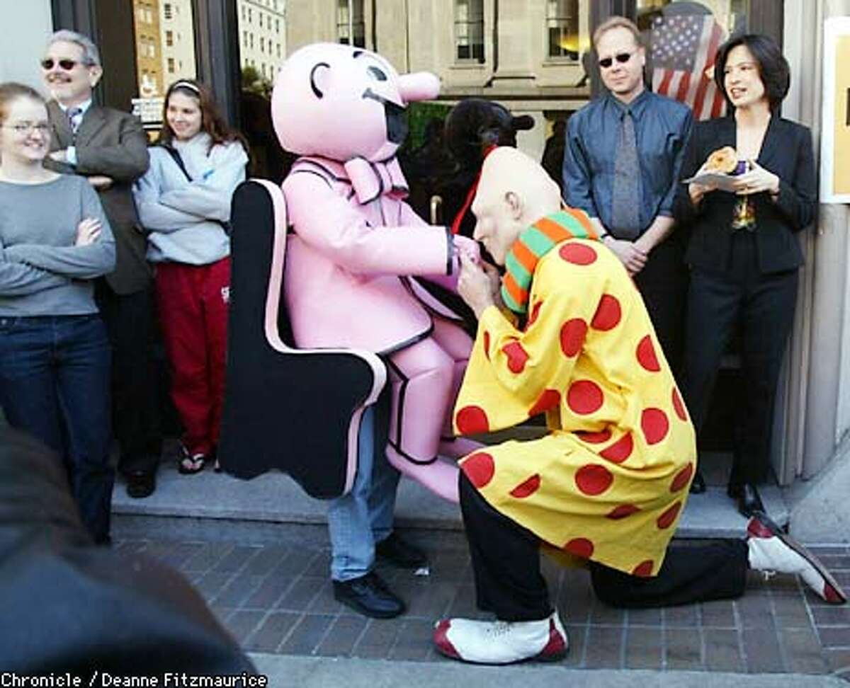 A man dressed as Zippy the Pinhead kisses the hand of the little man in the chair from the pink section in front of the San Francisco Chronicle. It was announced today that the Zippy comic will be brought back to the Chronicle after being briefly discontinued. CHRONICLE PHOTO BY DEANNE FITZMAURICE