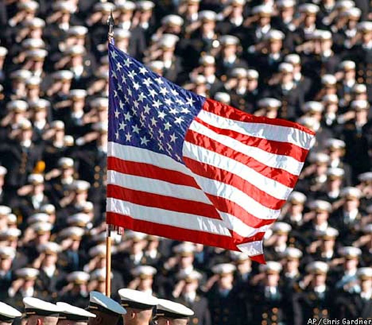 The American flag flies with a background of Navy midshipmen during the National Anthem at the 102nd Army Navy football game in Philadelphia Satuday, Dec. 1, 2001. (AP Photo/Chris Gardner)
