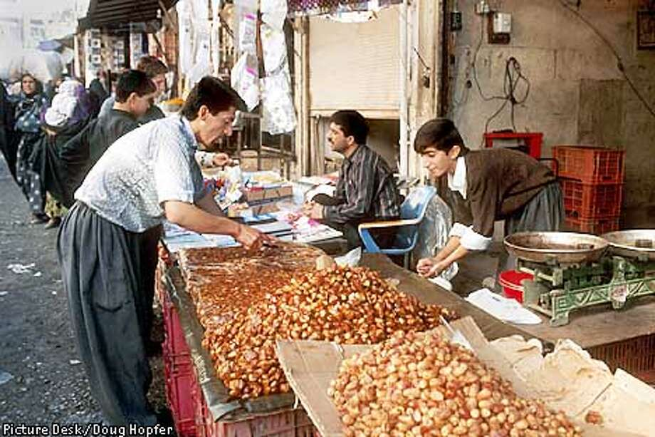 Northern Iraq. Street market vendors selling dates. Vendors would open their shop doors and trade and sell goods out on the sidewalks. At night they stored their goods behind roll down garage doors.   Photo: Doug Hopfer