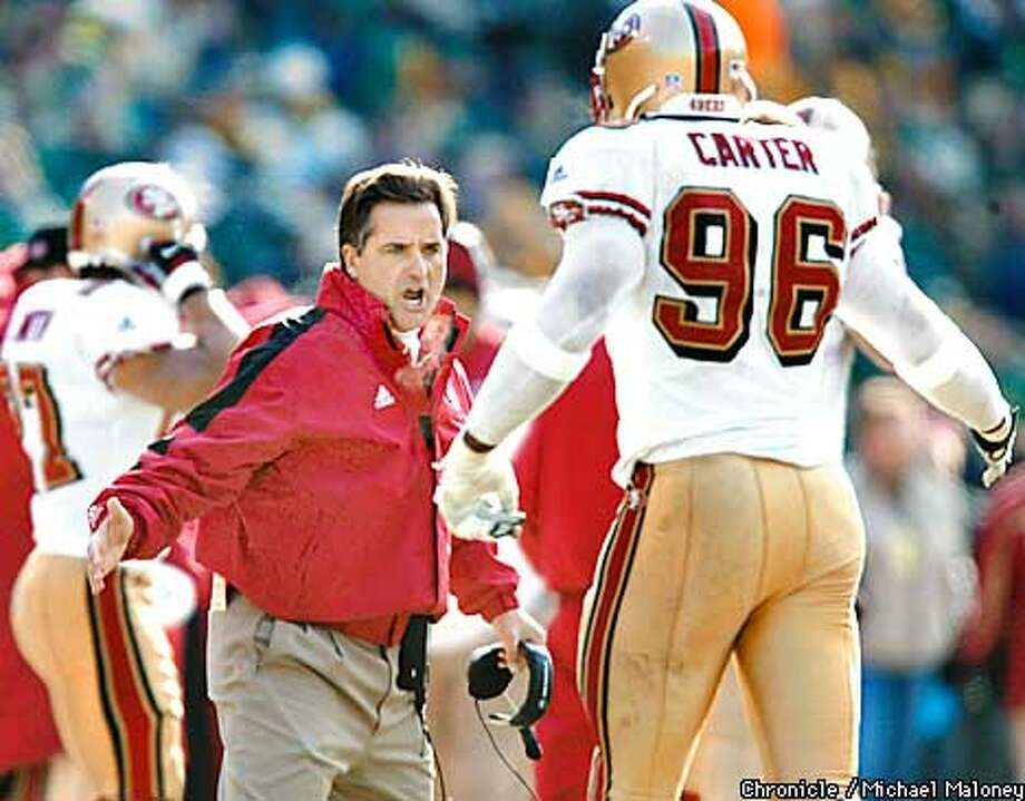 Head coach Steve Mariucci tries to fire up his defense in the 1st quarter. #96 DE Andre Carter.  SF 49ers vs Greenbay Packers at Lambeau Field in Green Bay. Packers won 25-15.  CHRONICLE PHOTO BY MICHAEL MALONEY Photo: MICHAEL MALONEY