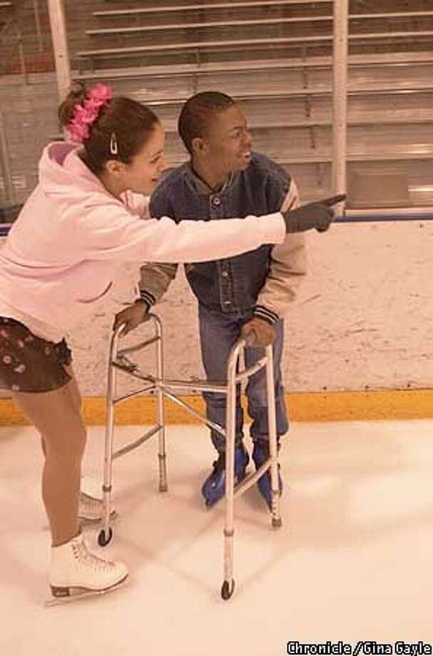 Natalie Koka,16, shows Christopher Morris how far around the rink he has come without falling during the Oakland Ice Center's program for special skaters. Photo by Gina Gayle/The SF Chronicle. Photo: GINA GAYLE