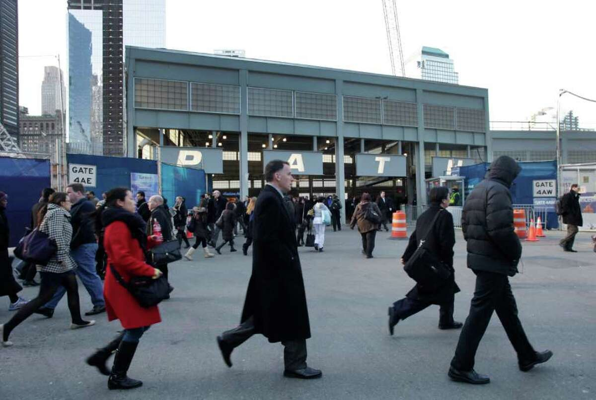 People pass through the temporary PATH commuter rail station at the World Trade Center, Tuesday, Jan. 31, 2012 in New York. The agency building the new World Trade Center says a design flaw could cost it millions of dollars. The problem is due to the temporary station. The Port Authority of New York and New Jersey said Tuesday the loading dock under One World Trade Center won't be finished in time for tenants to move their equipment into the 104-story tower. So it's building five temporary loading bays above ground. (AP Photo/Mark Lennihan)