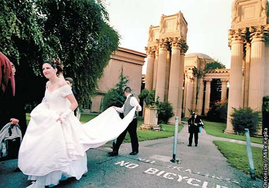 Sharon Doerhsen of Berkeley walks past past the Palace of Fine Arts after having her wedding photos taken at sunset. BY MIKE KEPKA/THE CHRONICLE Photo: MIKE KEPKA