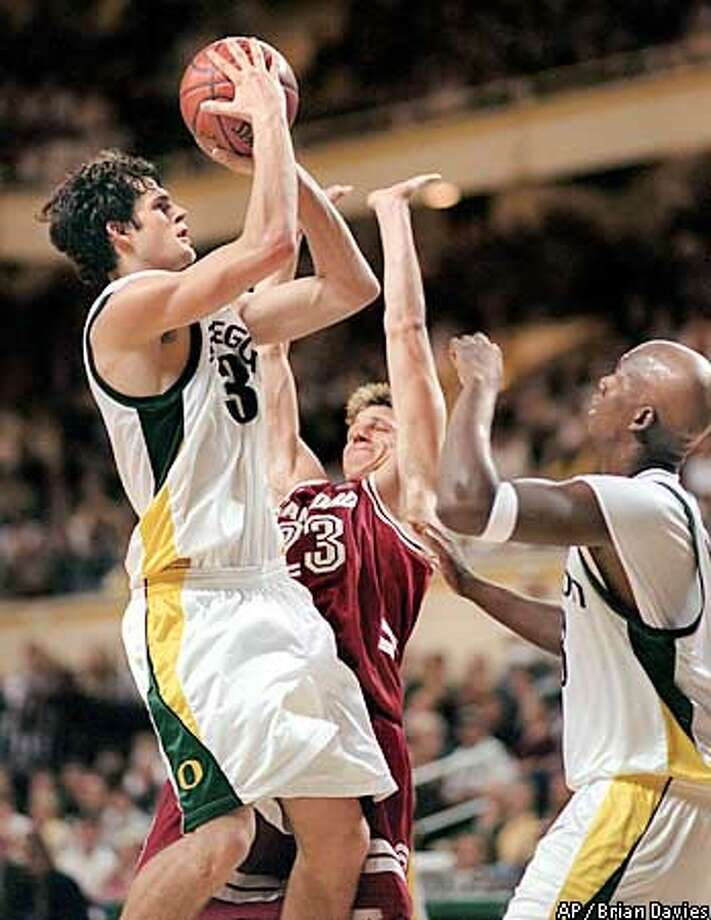 Oregon's Luke Jackson goes up for a shot against Stanford's Casey Jacobsen, center, Saturday, Jan. 12, 2002, in Eugene, Ore. At right is Oregon's Robert Johnson. Jackson had 27 points as Oregon defeated No. 14 Stanford 87-79. (AP Photo/Brian Davies) Photo: BRIAN DAVIES