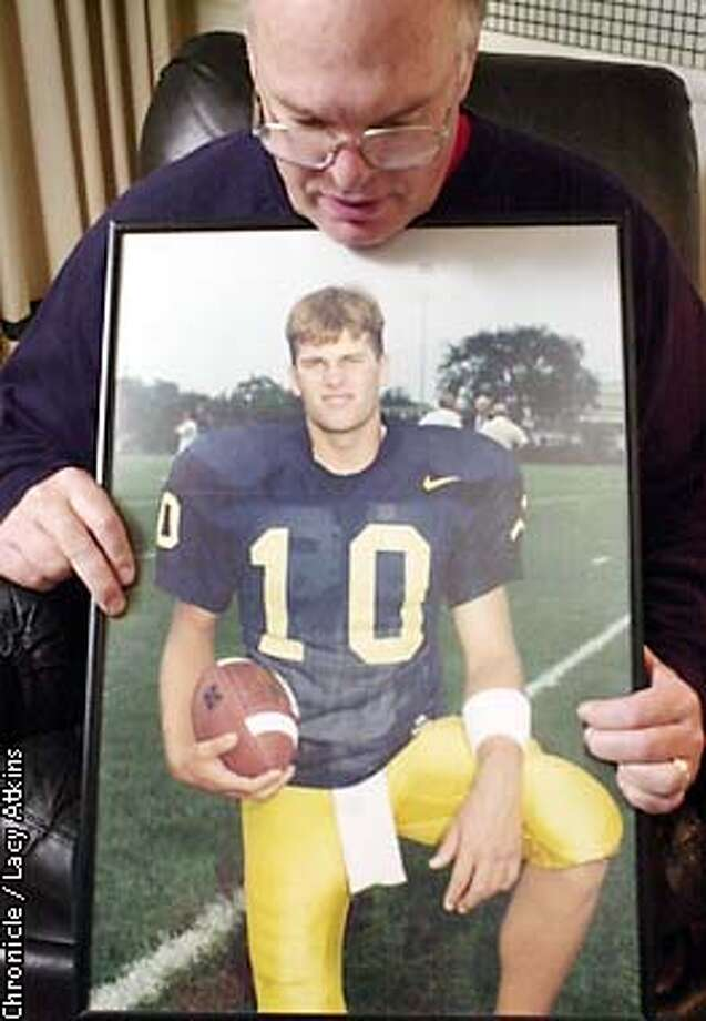 San Mateo's Tom Brady grew up idolizing 49ers quarterback Joe Montana. Here, Tom Brady Sr. holds a photo of his son when he was playing ball for Michigan. Photo: Lacy Atkins
