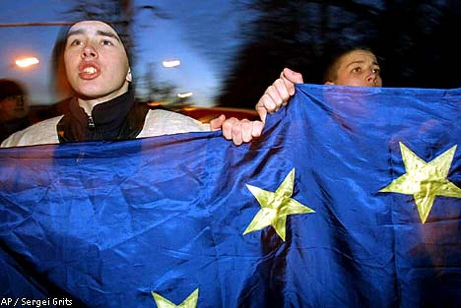 "Young demonstrators carry a E.U. flag and shout ""Long Live Belarus"" during a protest rally in downtown Minsk, Wednesday, Feb 14, 2001. A group of about 1,000 people protested against the rule of authoritarian President Alexander Lukashenko in Minsk on Wednesday, in what has become an annual Valentine's Day event. The action was the fifth Valentine's Day protest in Belarus, a small, former Soviet republic ruled since 1994 by Lukashenko, a heavy-handed leader who has closed newspapers, arrested opponentsand used riot police to break up protests. (AP Photo/Sergei Grits) Photo: SERGEI GRITS"