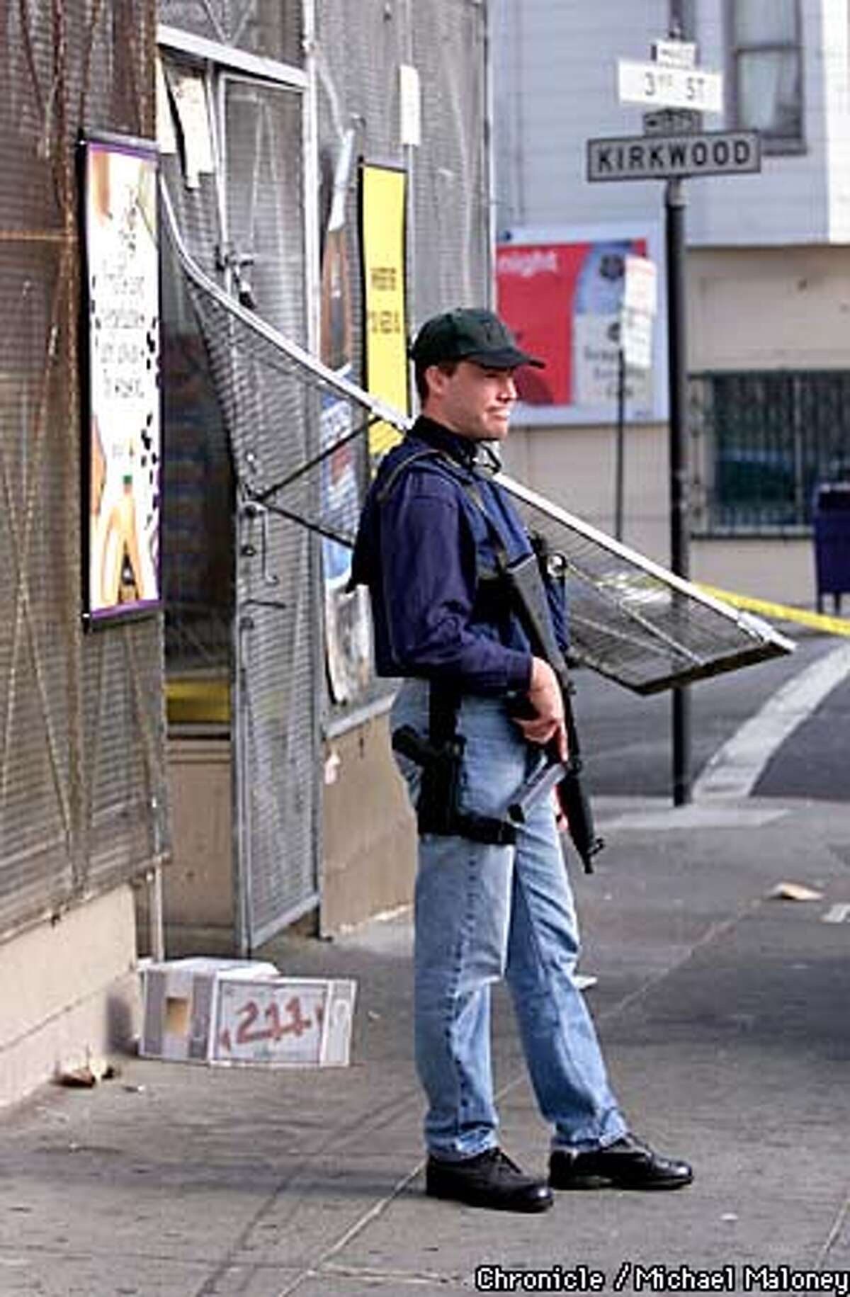 A heavily armed FBI agent stands guard outside the forced entryway of the Star Market at 4400 3rd Street in SF. SFPD and FBI agents were inside searching the liquor/grocery store. Starting at 6am this morning, nearly 200 FBI and bay area police officers carried out numerous search and arrest warrants to apprehend drug and weapons violators in SF and other bay area cities. CHRONICLE PHOTO BY MICHAEL MALONEY