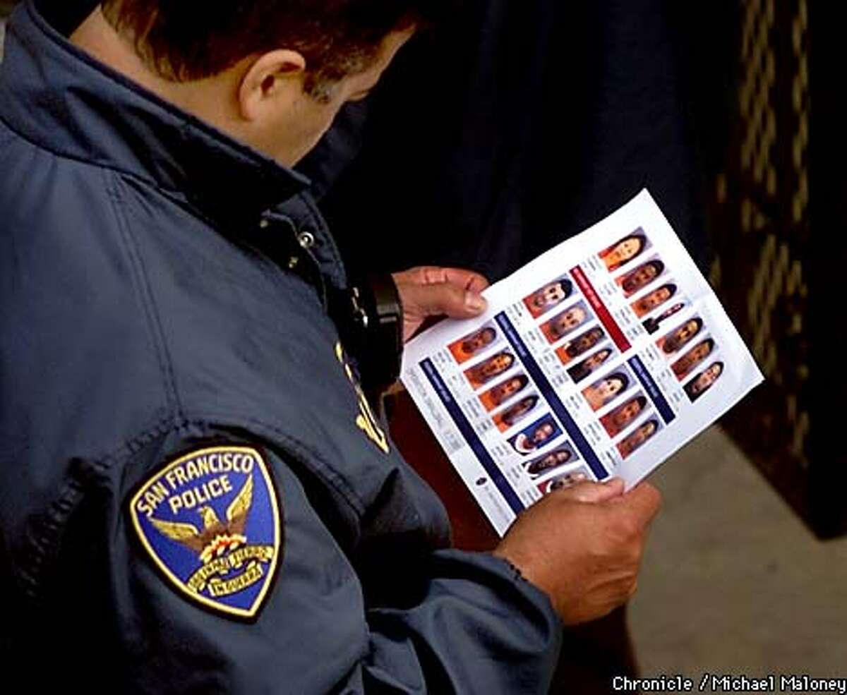 A SFPD officer looks at a mug sheet of suspects they are looking for in this mornings search. Starting at 6am this morning, nearly 200 FBI and bay area police officers carried out numerous search and arrest warrants to apprehend drug and weapons violators in SF and other bay area cities. CHRONICLE PHOTO BY MICHAEL MALONEY