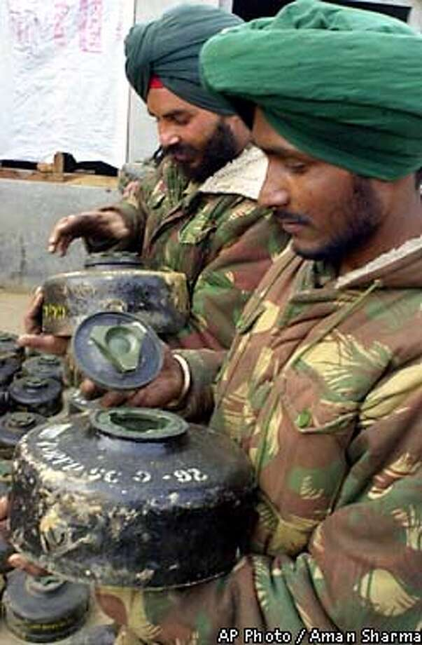 Indian Army soldiers prepare land mines and other explosives to spread into the fields of the Punjab region in India near the border of India and Pakistan Friday Jan. 4, 2002. India and Pakistan have pushed tens of thousands of troops to their 1,800-kilometer (1,100-mile) border since India accused Pakistan of supporting Islamic militants that attacked India's Parliament on Dec. 13, killing 14 people, including the five attackers. (AP Photo/Aman Sharma) Photo: AMAN SHARMA
