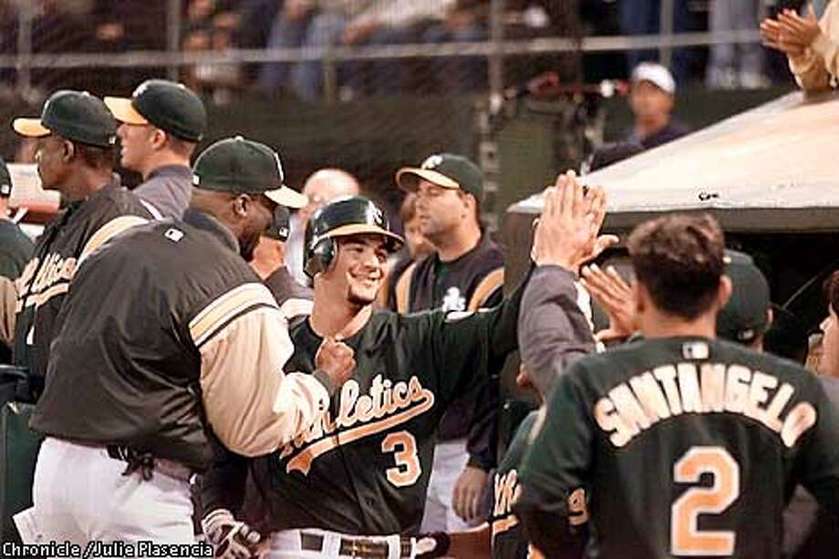 Oakland Athletic's third baseman Eric Chavez receives cheers from teammates after scoring a homerun and bringing two runners in at the bottom of the first inning in a match against the Baltimore Orioles at Network Collesium in Oakland.  (JULIE PLASENCIA/SAN FRANCISCO CHRONICLE) Photo: JULIE PLASENCIA