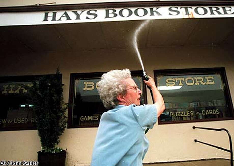 Elisabeth Hays hoses down her bookstore in Weaverville, Calif., Tuesday, Aug. 28, 2001, before being evacuated due too a fast-moving wildfire. The fire has forced the evacuation of the entire town. (AP Photo/Redding Record Searchlight, John Stubler) Photo: JOHN STUBLER