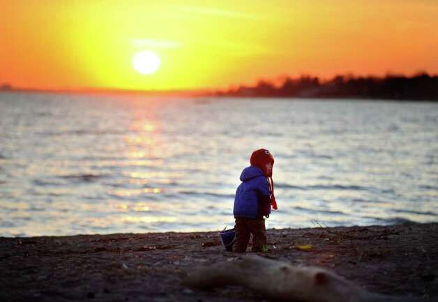 Two-year-old Coley Obringer, of Fairfield, plays in the sand at sunset Tuesday, Jan. 31, 2012 at Sasco Beach in Fairfield, Conn. Photo: Autumn Driscoll / Connecticut Post