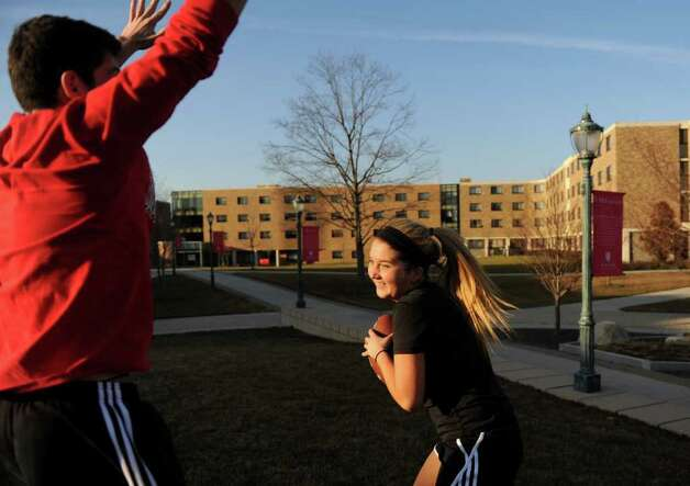 Fairfield University freshmen, Anthony Cucuzza, left, and Kristy McMahon take advantage of unseasonably mild temperatures Tuesday, Jan. 31, 2012 on the campus quad. Photo: Autumn Driscoll / Connecticut Post