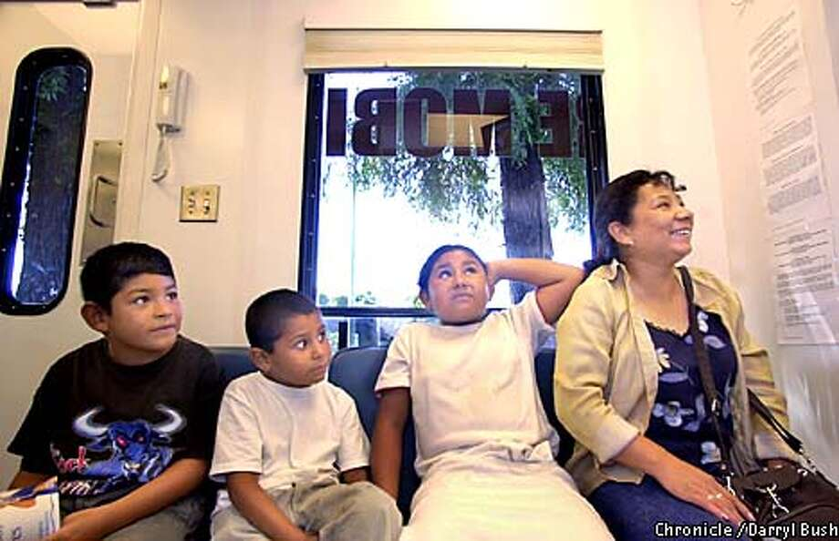Mom Maria Martinez, right, waits with her children from left: Jorge Navarro,7, Carlos Navarro, 7, and Sylvia Navarro, 9, as they wait their turn for teeth cleaning inside the Dental Care Mobile unit parked inside the Santa Clara Valley Medical Center in San Jose. Chronicle Photo by Darryl Bush Photo: Darryl Bush