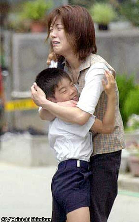 A Japanese schoolboy is hugged by his mother at Ikeda Elementary School in Ikeda, western Japan, on Friday, June 8, 2001, where a knife-wielding attacker killed eight children. The attacker, a 37-year-old unemployed man, Mamoru Takuma, walked into the school earlier in the day and wordlessly began slashing students before being arrested. (AP Photo/Tsutomu Koseki, Mainichi Shimbun)==JAPAN OUT, , NO INTERNET, CREDIT MANDATORY== Photo: TSUTOMU KOSEKI