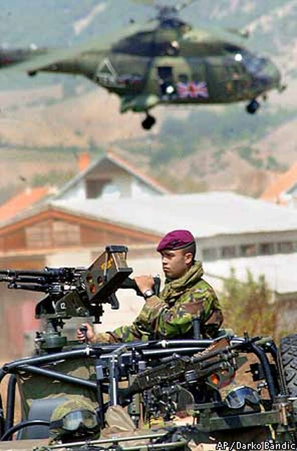 A British soldier is securing weapons collection as a British Army helicopter flies overhead in the village of Otlja, some 30 kilometers (18 miles) northwest of the capital Skopje, , Monday, Aug. 27, 2001. NATO has started Operation Essential Harvest, collecting weapons from the ethnic Albanian rebels. (AP Photo/Darko Bandic) Photo: DARKO BANDIC