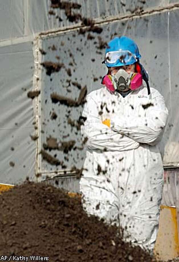 A worker dressed in a full hazmat suit and respirator watched debris from the World Trade Center fall at the Fresh Kills landfill in Staten Island, N.Y. Associated Press photo by Kathy Willens