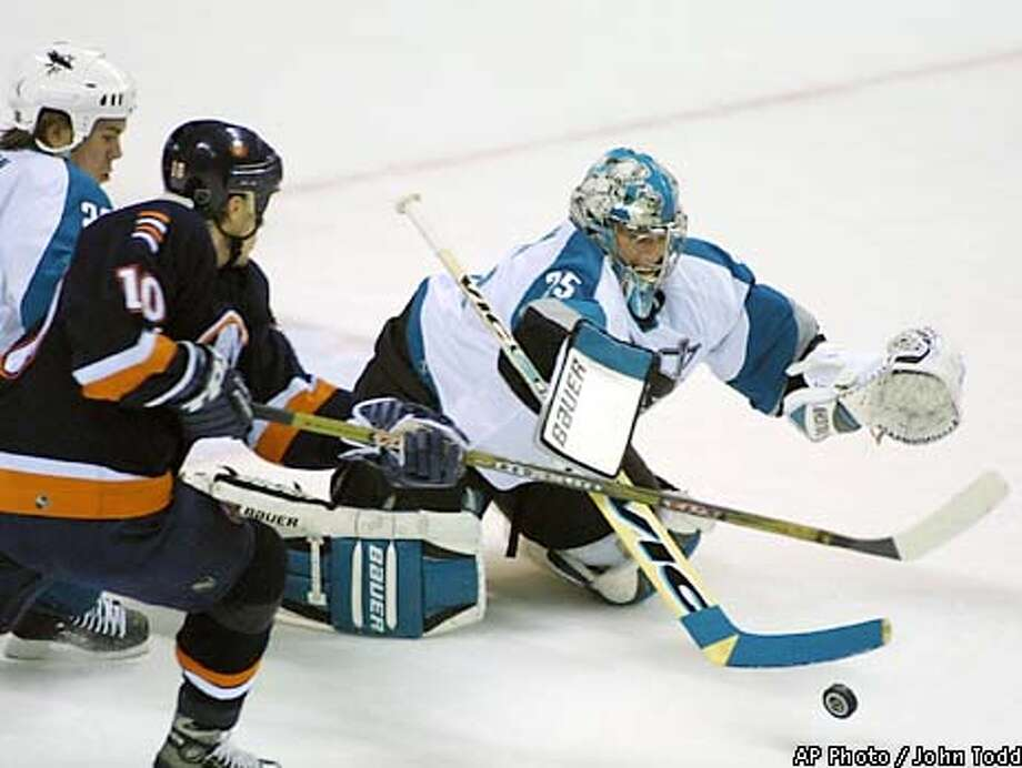 New York Islanders center Mats Lindgren (10) of Sweden tries to shoot on San Jose Sharks goalie Evgeni Nabokov (35) of Kazakhstan during a scramble for a loose puck in the first period Thursday, Jan. 17, 2002, in San Jose, Calif. Sharks' Scott Hannan is at far left. (AP Photo/John Todd) Photo: JOHN TODD