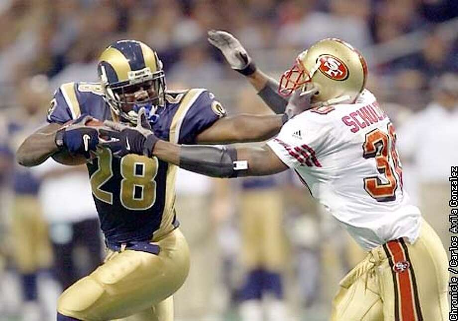 The St. Louis Rams' Marshall Faulk, gets by the San Francisco 49ers' Lance Shulters in the first quarter on a short run that set up a rushing touchdown by Faulk several plays later as the 49ers lost to the Rams at St. Louis on Sunday, December 9, 2001.  (Photo by Carlos Avila Gonzalez/The San Francisco Chronicle) Photo: CARLOS AVILA GONZALEZ