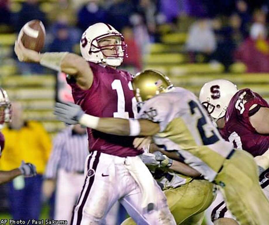 Stanford quarterback Randy Fasani lets off a pass as he is tackled by Notre Dame free safety Donald Dykes in the third quarter, Saturday, Nov. 24, 2001 in Stanford, Calif. (AP Photo/Paul Sakuma) Photo: PAUL SAKUMA