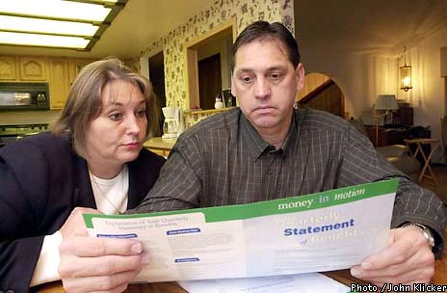 """Diane and Joe Rinard who both work for PGE an Enron company look over """"Money in Motion"""" an Enron quarterly report of employees investments, Wed. Jan. 16, 2002 at their home in Gresham Ore., but the only motion the Rinards have seen is a downward spiral to six cents a share. (Photo byJohn Klicker)"""