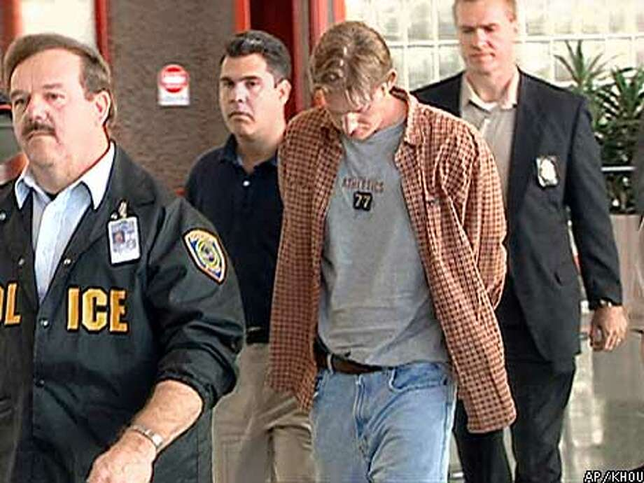 "Christian Longo, center head down, is shown in this video image after arriving in Houston, Texas, Monday, Jan. 14, 2001. Longo, accused of killing his wife and three children last month and dumping their bodies into the Pacific, was captured near Tulum, Mexico, a resort town 60 miles south of Cancun, after the FBI placed him on its ""Ten Most Wanted Fugitives"" list. (AP Photo/KHOU)"