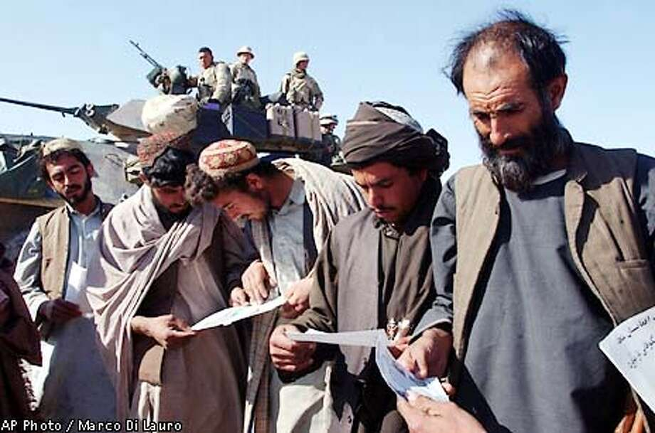Afghans read flyers seeking information about al-Qaida members and Taliban authorities after receiving them from U.S. Marines on patrol outside of the American military compound near Kandahar, Afghanistan Thursday, Jan. 10, 2002. More than three months after the beginning of American offensive in Afghanistan, most of the high-ranking Taliban and al-Qaida officials still remain at large. (AP Photo/Marco Di Lauro) Photo: MARCO DI LAURO