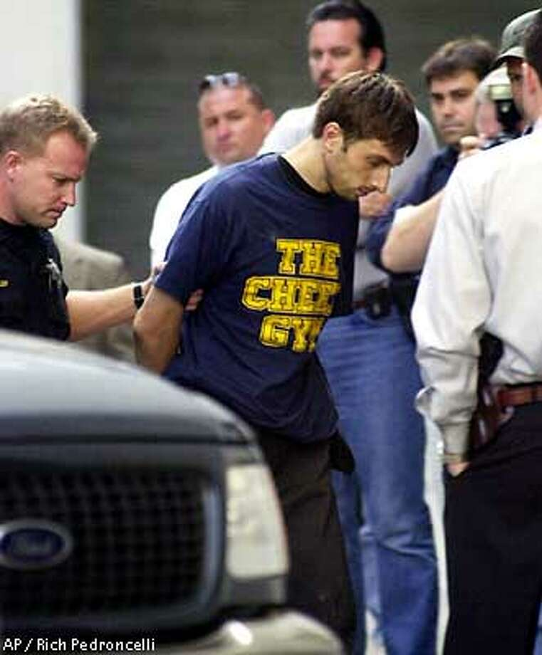 Multiple murder suspect Nikolay Soltys, center, is surrounded by Sacramento County Sheriff's deputies as he is taken into the Sheriff's office in Sacramento ,Calif., Thursday, Aug. 30, 2001. Soltys, who had been on the run for 10 days since for allegedly slashing the throats of his pregnant wife, 3-year-old son and four other relatives, was captured at his mother' s house in Citrus Heights, a suburb of Sacramento, Calif. (AP Photo/Rich Pedroncelli) Photo: RICH PEDRONCELLI