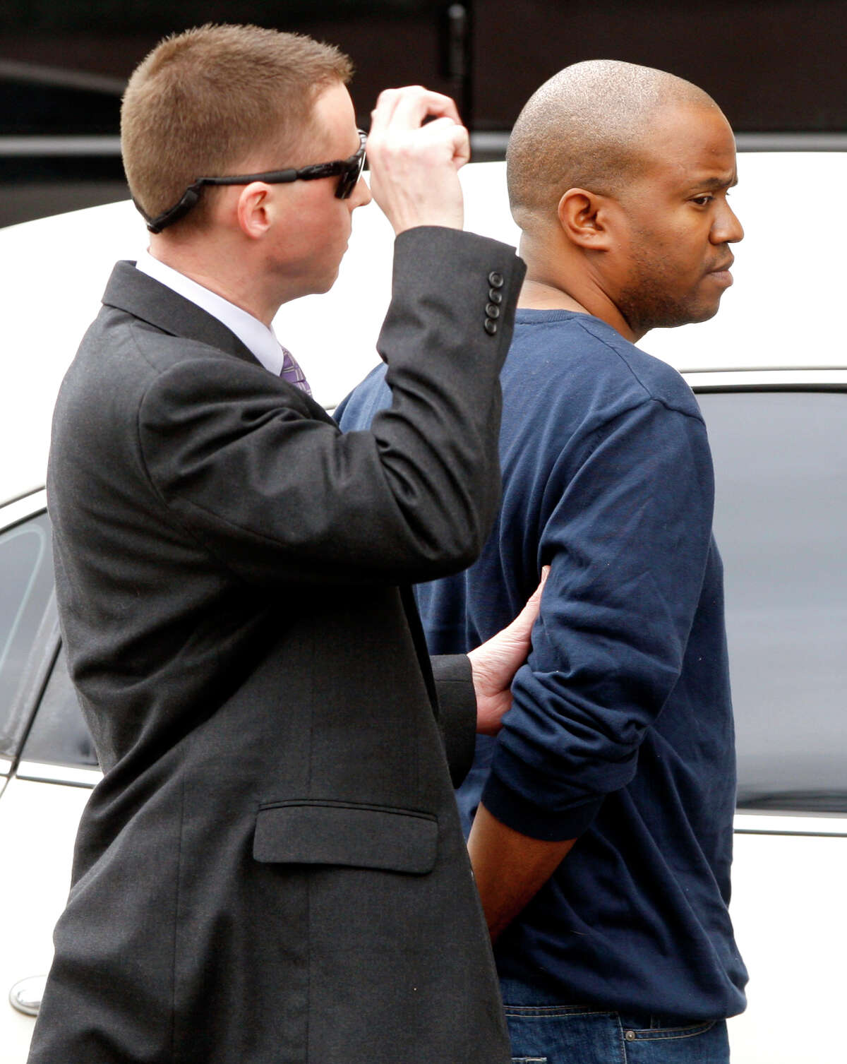 FBI agents take Gemase Simmons to federal court in San Antonio on Tuesday, Jan. 31, 2012, after he was arrested on federal child-porn related charges. Simmons was featured in a news segment on Dateline alleging he scammed several youths into believing they were being filmed for a reality show about modeling.