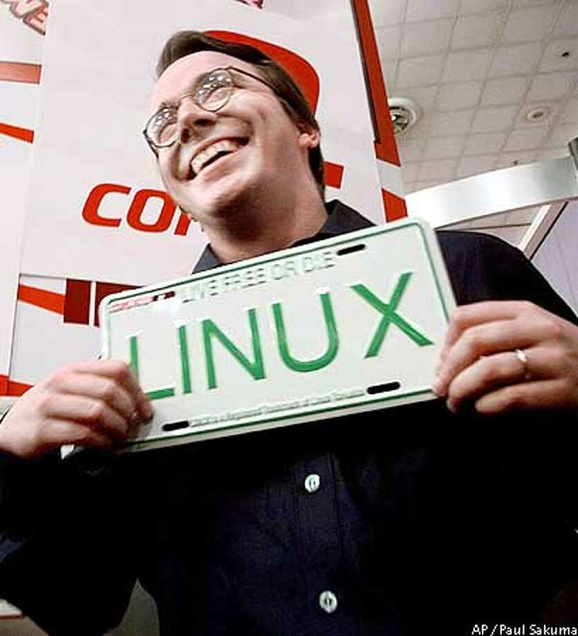FILE--Linus Torvalds, creator of the Linux computer operating system, holds an auto license plate with the Linux name at the Linux World Conference in San Jose, Calif., March 2, 1999. Linux, a possible alternative to Microsoft's dominant Windows operating system, is distributed by Red Hat Software Inc., which is expected to offer its shares to the public for the first time in early August. (AP Photo/Paul Sakuma) Photo: PAUL SAKUMA