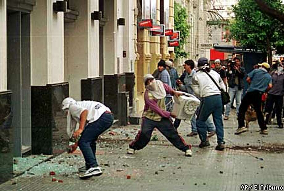 Rioters in Argentina shattered bank windows during violent outbursts produced by the banking freeze. El Tribuno photo via Associated Press