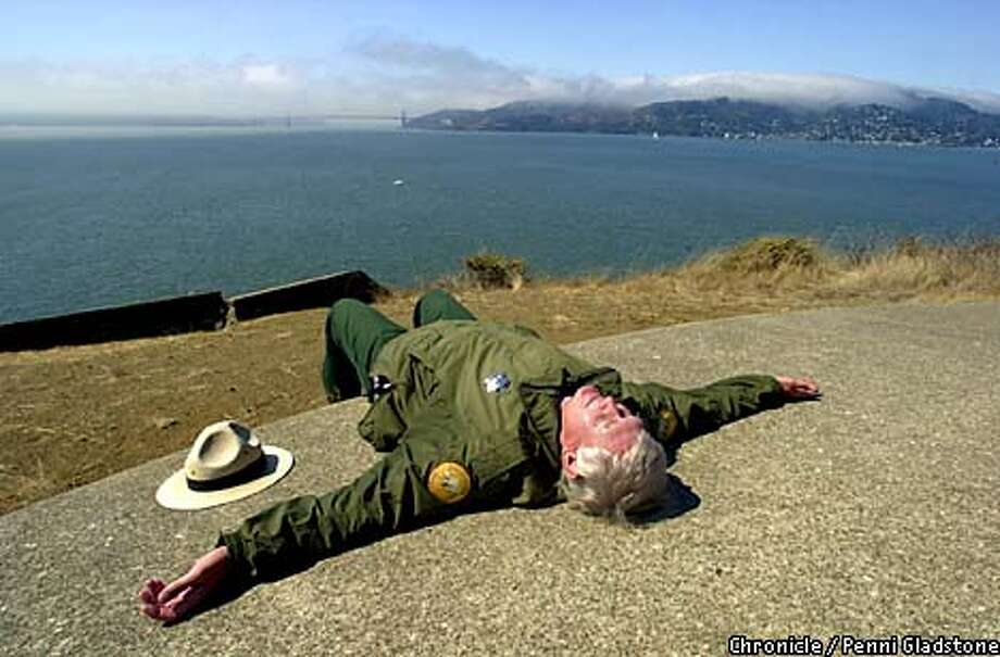 """With a foggy view of the GG Bridge & Sausalito, Dan soaks up the heat of the concrete at Battery Ledyard at Camp Reynolds, west garrison. Ranger Dan Winkelman is famous throughout the Bay Area because he is featured as presidential candidate for the Peace and Quiet Party in the cartoon """"Farley.'' today is his last day to work on Angel Island as he is retiring tomorrow. CHRONICLE PHOTO BY PENNI GLADSTONE Photo: Penni Gladstone"""