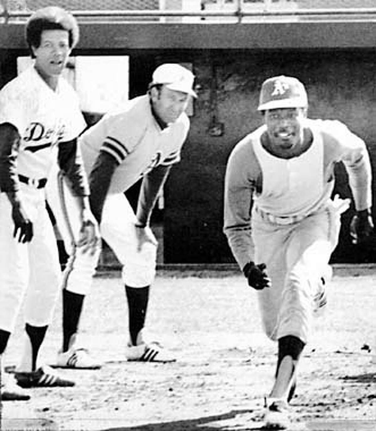 Herb Washington, hired especially as a runner by Charles O. Finley of the Oakland A's breaks away from first base under the watchful eyes of Maury Wills.