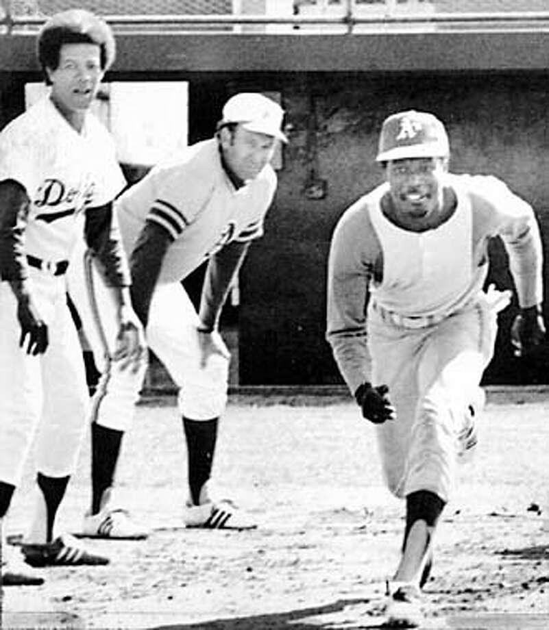 Herb Washington, hired especially as a runner by Charles O. Finley of the Oakland A's breaks away from first base under the watchful eyes of Maury Wills. Photo: HANDOUT