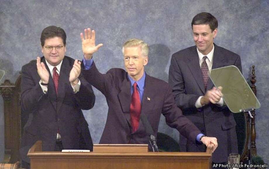 California Gov. Gray Davis, center, waves to members of the Legislature and guests as Assembly Seaker Robert Hertzberg, D-Van Nuys, left, and State Sen.Jack O'Connell, D-Santa Barbara, applaud before Davis delivered his address at the Capitol in Sacramento, Calif., Tuesday, Jan. 8, 2002. Davis said said his budget proposal will not include a tax increase to close a projected $12.4 billion budget deficit. (AP Photo/Rich Pedroncelli) Photo: RICH PEDRONCELLI