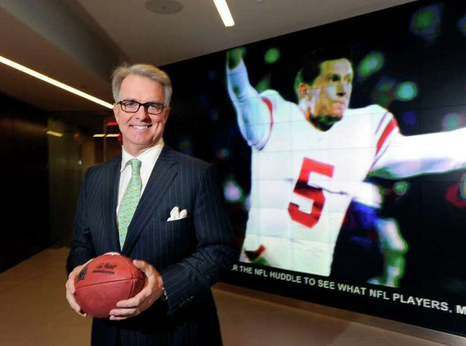 Greenwich resident Paul Hicks III, executive vice president of communications and government affairs for the National Football League, in front of a large video screen image of New York Giants punter and placeholder Steve Weatherford reacting to the Giants game-winning field goal against the 49ers that sent the team to this year's Super Bowl, in the lobby of the NFL offices in New York City, Tuesday afternoon, Jan. 31, 2012. Photo: Bob Luckey / Greenwich Time