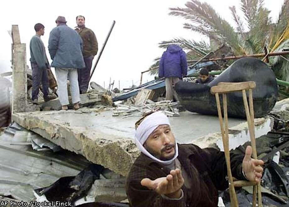 Mohammed El Bakry, foreground, sits in the remains of his home after the homes in his area were destroyed last night, according to the residents, by Israeli bulldozers in Rafah, southern Gaza Strip, Thursday, Jan. 10, 2002. Two Palestinians armed with grenades and assault rifles stormed an Israeli army post at Kerem Shalom near the Gaza Strip early Wednesday, killing four soldiers before being shot dead in a gun battle. (AP Photo /Jockel Finck) Photo: JOCKEL FINCK