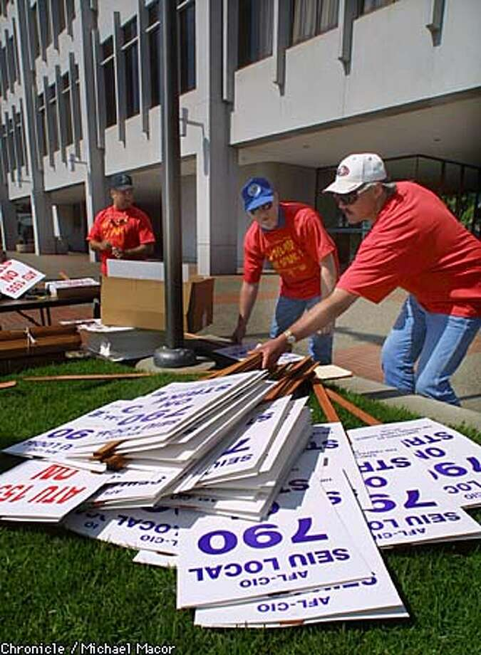 BART workers in front of BART Headquarters in downtown Oakland, make pickets sings in preparation for a strike is negotiations fail. Workers Greg Appleby, left and Steve Basinger consrtruct a pile of signs. by MIchael Macor/The Chronicle Photo: MICHAEL MACOR