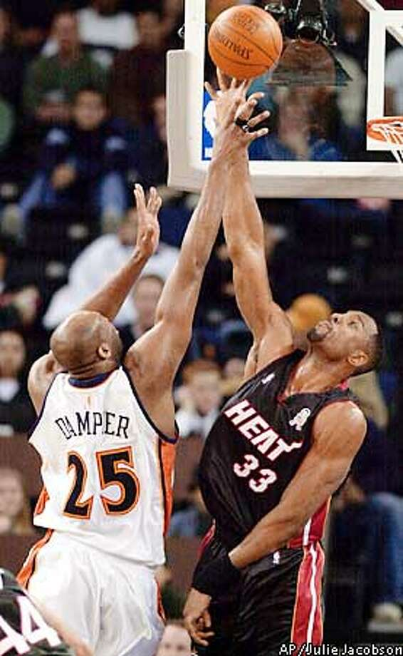 Miami Heat center Alonzo Mourning, right, blocks a shot attempt by Golden State Warriors center Erick Dampier during the first quarter Monday, Jan. 14, 2002, in Oakland, Calif. (AP Photo/Julie Jacobson) Photo: JULIE JACOBSON